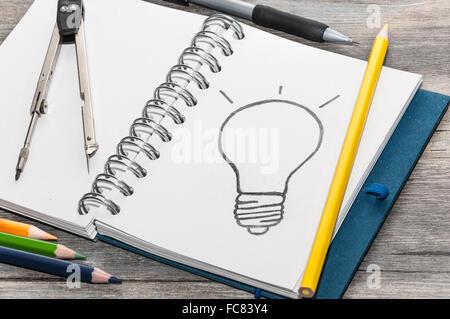 Buchen Sie mit einer Zeichnung einer Glühbirne - Stockfoto