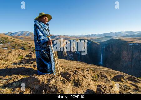 Ein lokaler Schafhirte konvergiert auf den Klippen der Maletsunyane-Wasserfall im ländlichen Lesotho. - Stockfoto
