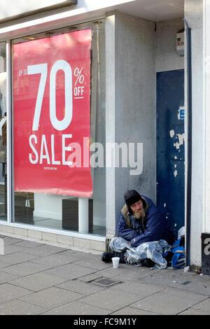 Obdachlosen Mann sitzt in einer Stadt Zentrum Tür England uk - Stockfoto