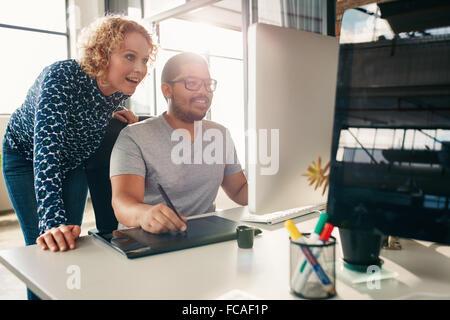 Zwei junge kreative Arbeiten zusammen an einem neuen Projekt im Büro. Männliche und weibliche Designer mit digitalen - Stockfoto