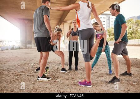 Gruppe junger Freunde Dehnung unter einer Brücke nach einem Morgenlauf. Club-Gruppe, die eine Pause vom Training - Stockfoto