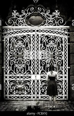Rückansicht der Frau stand vor großen geschlossenen Toren