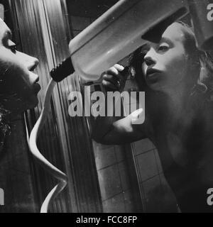 Junge Frau, die Anwendung von Mascara beim Spiegel betrachten - Stockfoto