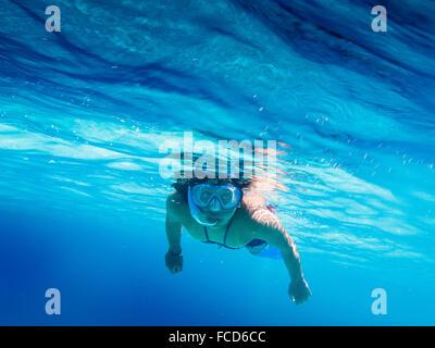Porträt der Frau im blauen Meer schwimmen - Stockfoto