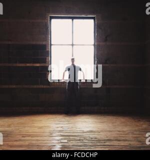 Mann an einem Fenster gelehnt