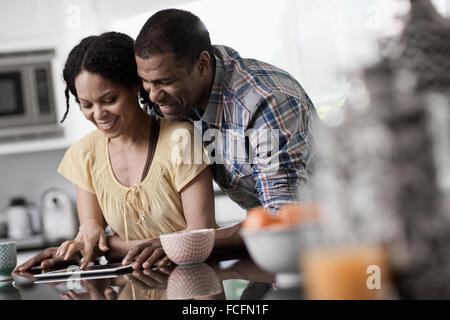 Ein Mann und eine Frau, paar in Ther Küche sowohl Blick auf eine digital-Tablette. - Stockfoto