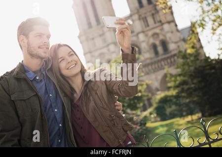 Zwei Menschen, ein paar stehen dicht beieinander unter einem selfy außerhalb der historischen Kathedrale Notre Dame - Stockfoto