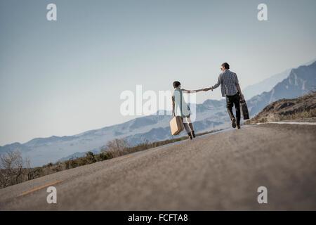 Ein junges Paar, Mann und Frau gehen hand in Hand auf eine asphaltierte Straße in der Wüste Tragetaschen. - Stockfoto