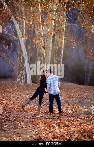 Paar zu Fuß entfernt, in einem Wald spielerisch küssen - Stockfoto