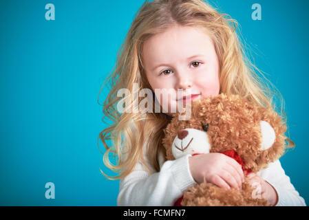 Fabelhaftes kleines Mädchen umarmt brauner Teddybär. - Stockfoto