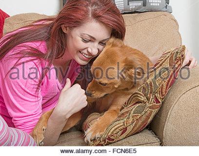 Schöne rothaarige Frau kuschelt mit ihrem Hund auf couch - Stockfoto