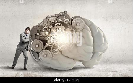 Junger Geschäftsmann stützte sich auf große Gehirn Modell - Stockfoto