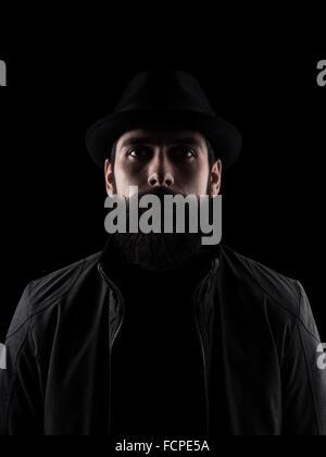 Bärtiger Mann mit schwarzem Hut, Blick in die Kamera. Hoher Kontrast niedrig Schlüssel dunkler Schatten Porträt - Stockfoto