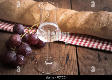 italienischen Grappa mit Trauben und Brot auf Holztisch - Stockfoto