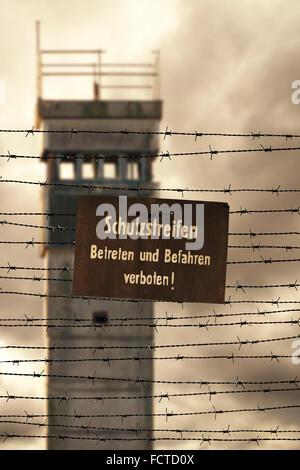 Wachturm mit Stacheldraht und Verbotszeichen an der ehemaligen innerdeutschen Grenze - Stockfoto