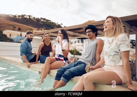 Junge Leute trinken Cocktails am Pool während der Partei. Junge Freunde lachen während der Sitzung von einem Schwimmbad. Männer und Frauen