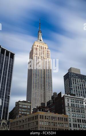 Langzeitbelichtung des Empire State Building Wolkenkratzers mit Top beleuchtet von der Sonne an einem bewölkten - Stockfoto