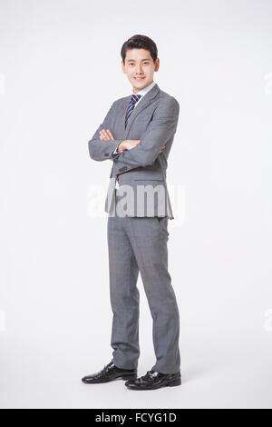Mann in Anzug und Krawatte im Retro-Stil stehen mit verschränkten Armen und starrte nach vorne mit einem Lächeln - Stockfoto