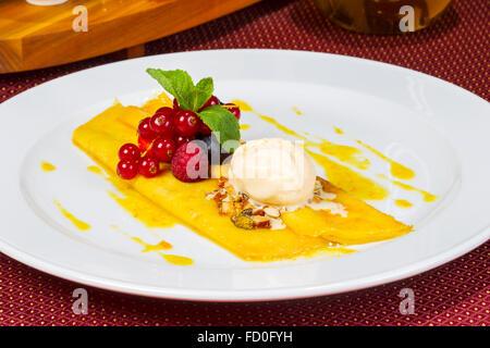 Schönen Pfannkuchen mit Honig und servieren Eis, verziert mit Nüssen, frischen Beeren. - Stockfoto