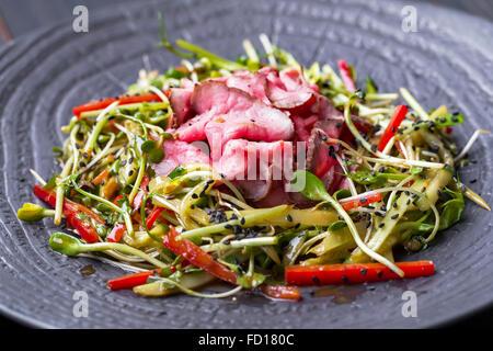 Authentische Salat mit Speck, frische rote Paprika, Sprossen, Sesam und Olivenöl auf einer schwarzen Platte. Morgen stimmungsvolle Beleuchtung,