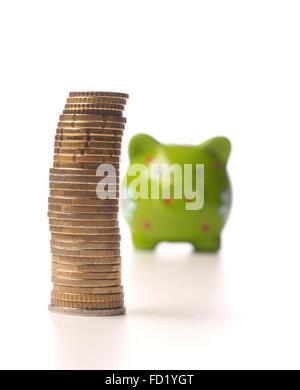 Gestapelte Euro-Münzen vor ein lustiges Sparschwein auf weiß - Stockfoto