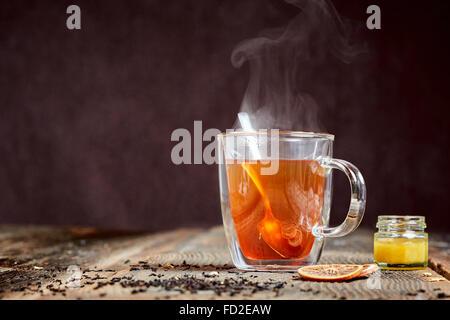 Dampfend heißen Tee mit Honig und zwei Orangenscheiben auf einem Holztisch - Stockfoto