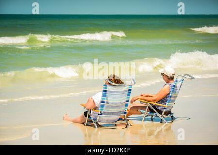 Zwei Frauen sitzen in ihren Strandkörben mit ihren Beinen in der Brandung an der Küste und beobachten die Wellen - Stockfoto