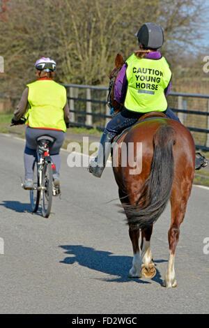 Junge Pferd und Reiter tragen hohe vis Nachricht Weste mit Begleiter reiten entlang country lane Bridge - Stockfoto