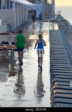 Am frühen Morgen Jogger trainieren mit Sorgfalt entlang engagierten Kreuzfahrtschiff, die Schaltung zwischen Sonnenliegen - Stockfoto