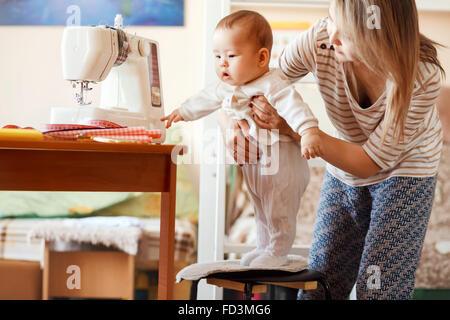 Mutter und Kind, zu Hause, die erste Gehversuche, natürliches Licht. Baby-/Kinderbetreuung kombiniert mit Arbeit - Stockfoto