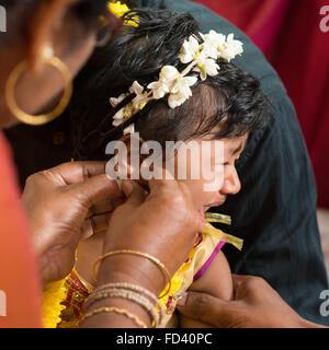 Traditionelle indisch-hinduistischen Familie Ohrlochstechen Zeremonie für Babymädchen in ein Jahr alt. - Stockfoto