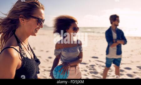 Lächelnde junge Frau und Freunden am Strand mit Volleyball spielen. Junge Menschen, Sommerurlaub am Strand genießen.