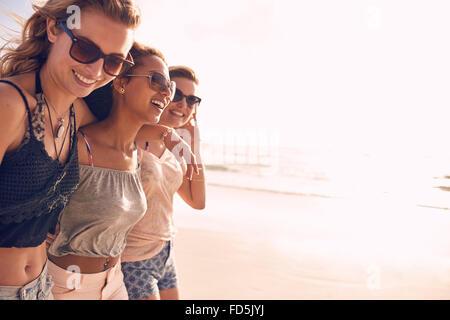 Gruppe von schönen jungen Frauen an einem Strand spazieren. Drei Freunde zu Fuß am Strand und lachend auf einem - Stockfoto