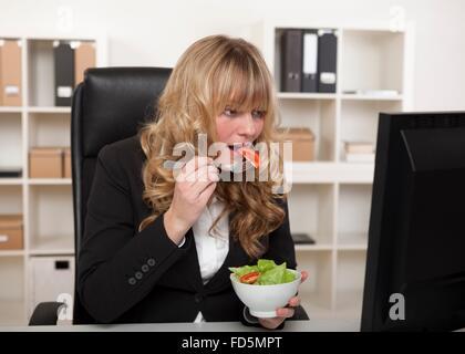 Geschäftsfrau mit einem schnellen Snack an ihrem Schreibtisch einen gesunden Salat zu essen, da sie weiter lesen - Stockfoto