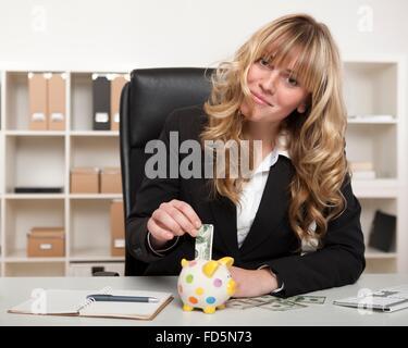 Glücklich erfolgreiche junge Geschäftsfrau sparen für den Ruhestand Platzierung einer gefalteten Euro-Banknote in - Stockfoto