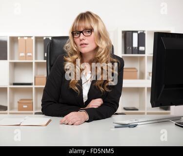 Junge Geschäftsfrau oder Managerin in Gläsern sitzt an ihrem Schreibtisch im Büro erwartungsvoll in die Kamera schaut - Stockfoto