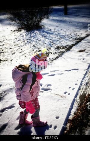 Niedliche Mädchen gehen auf Schnee bedeckt Landschaft im Winter - Stockfoto