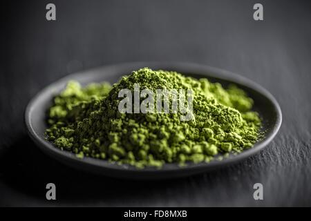 Macha grünen Pulver in einer Platte auf schwarzem Hintergrund - Stockfoto