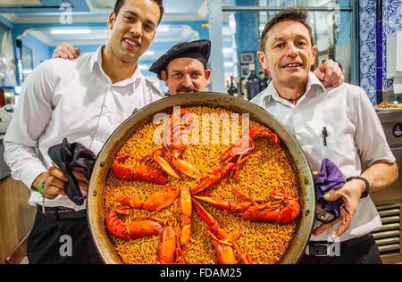Kellner zeigen eine Paella. In La Pepica Restaurant, 6 Passeig Neptú Malvarrosa Strand. Valencia, Spanien. - Stockfoto