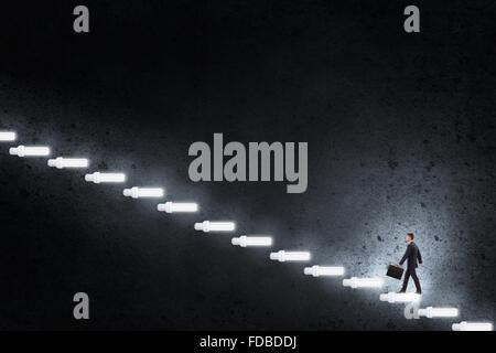 Junger Geschäftsmann zu Fuß auf der Treppe von Glühbirnen, die stellvertretend für Erfolgskonzept - Stockfoto