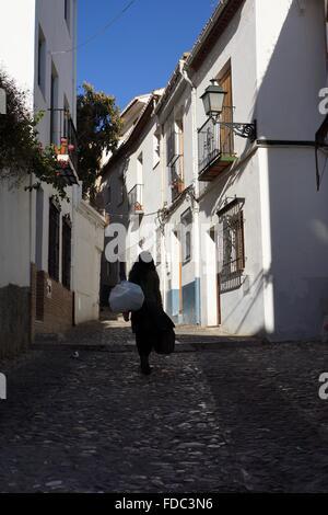 Dame zu Fuß durch die Straßen der Altstadt von Granada, Spanien - Stockfoto