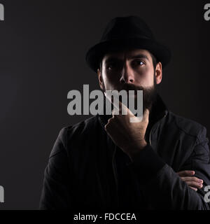 Hoher Kontrast Porträt von Ernst bärtigen Mann mit schwarzen Hut denken Blick in die Kamera über schwarzen Hintergrund. - Stockfoto