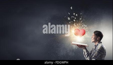 Junger Mann mit geöffneten Buch in Händen und rotes Herz auf Seiten - Stockfoto