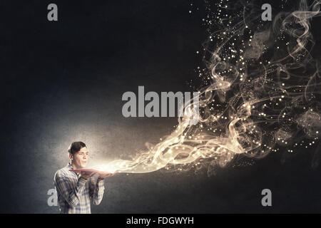 Junger Mann mit geöffneten Buch in Händen weht auf Seiten - Stockfoto