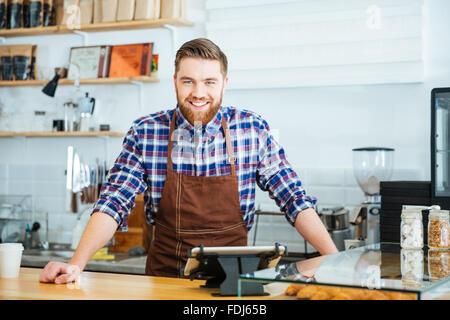 Potrait glücklich schöne Barista im karierten Hemd und braune Schürze stehen im Coffe-shop - Stockfoto