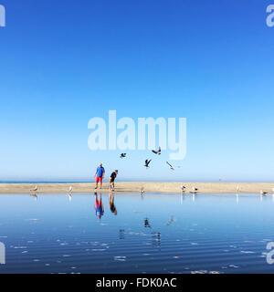 Mann und zwei Söhne stehen am Strand - Stockfoto
