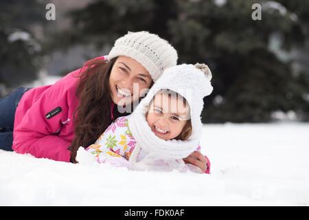 Glückliche Mutter und Tochter im Schnee liegen - Stockfoto