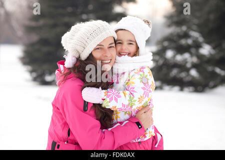 Porträt einer lächelnden Mutter und Tochter im Schnee, Sofia, Bulgarien - Stockfoto
