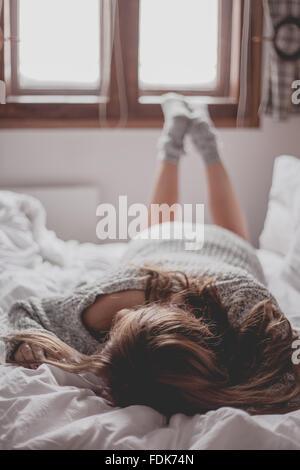 Frau, Gesicht nach unten auf einem Bett liegend - Stockfoto