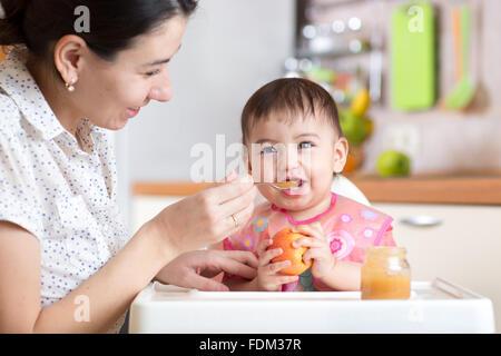 Baby Kind sitzt im Stuhl mit einem Löffel und gesunder Ernährung - Stockfoto